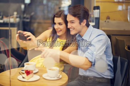happy couple taking photo in cafe