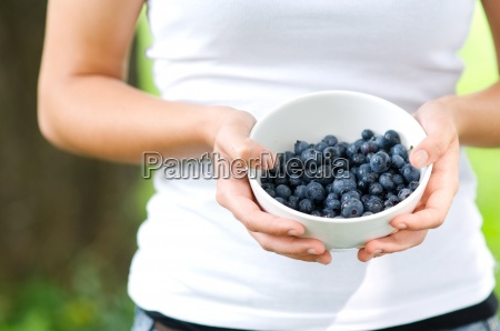 young woman holding bowl filled blueberries