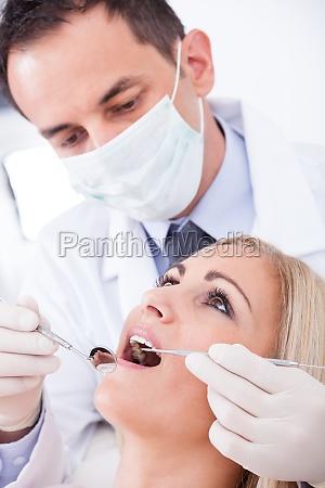 dentista paciente que examinam