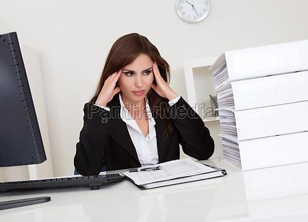 overworked businesswoman in office