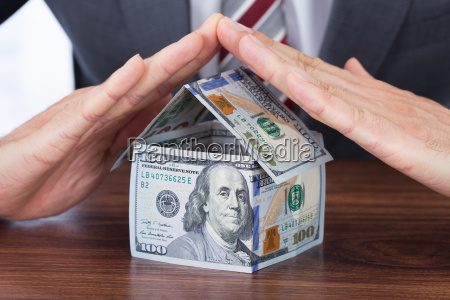 businessman sheltering house made with bank