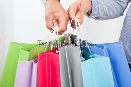 couples hands holding multicolored shopping bags