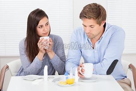 sick couple drinking lemon tea at