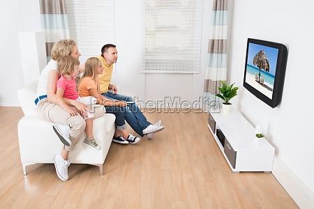 familia jovem assistindo tv juntos