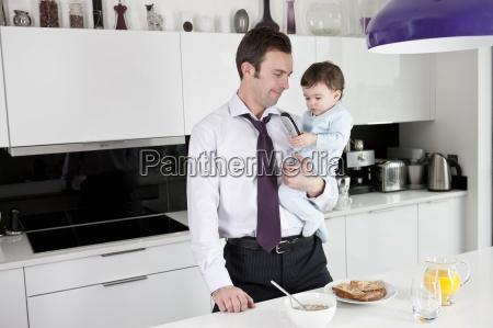 um pai tentando usar o telefone