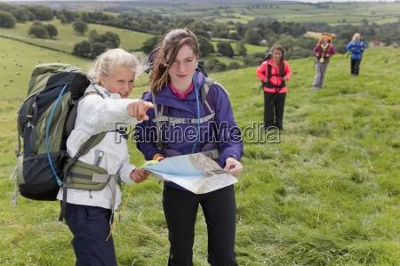 meninas com mochilas bussola e mapa