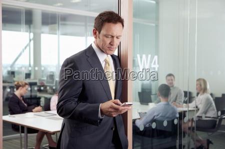 alvorlig tekst forretningsmand messaging pa mobiltelefon