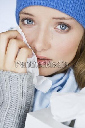 uma jovem mulher chorando enxugando as