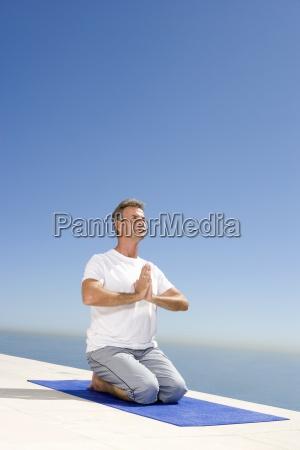 aeldre mand meditere pa traeningsmatte udendors