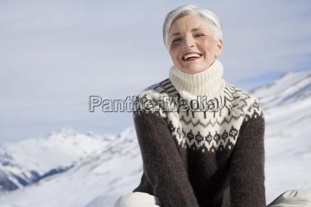 mulher madura feliz sentado nas montanhas