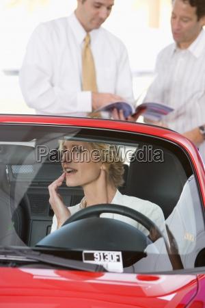 mulher sentada no conversivel vermelho na