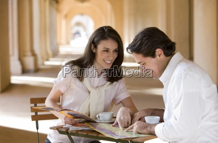 couple sitting at pavement cafxc3xa9 table