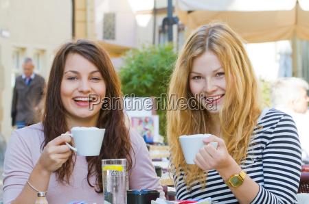 duas mulheres novas no cafe da