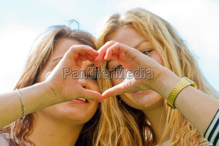 two girlfriends make a finger heart