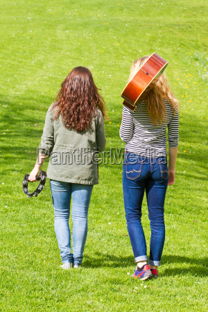 two teenagers with musical instruments