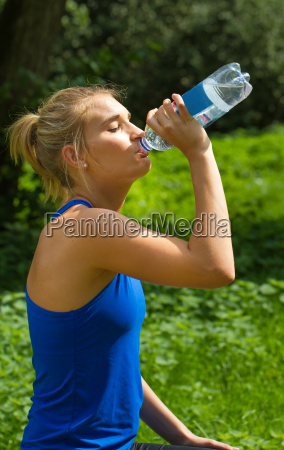 young woman drinking after sports