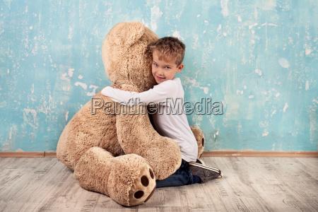 child cuddling with teddy bear