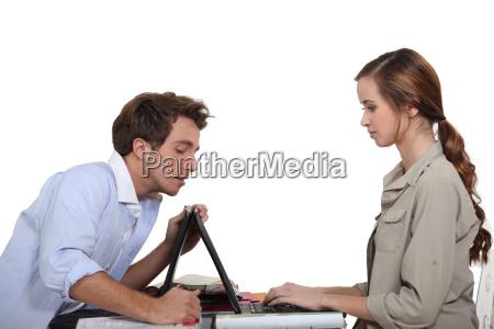 homem que ajuda senhora com laptop