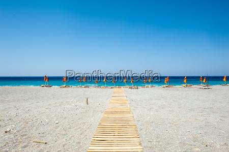 praia com guarda sois e espreguicadeiras
