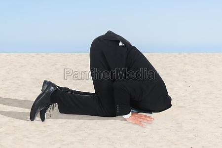 empresario escondendo a cabeca na areia