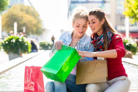 kvinder shopping med indkobsposer i byen