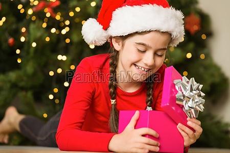 menina que abre um presente no