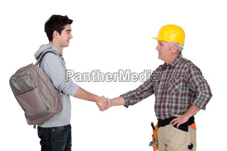 builder shaking apprentices hand
