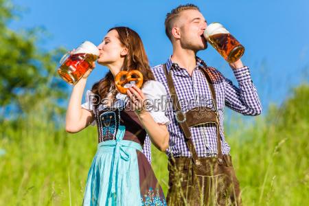 casal alemao em traje com cerveja