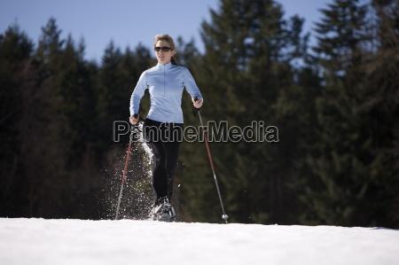 jovem mulher corre atraves da neve