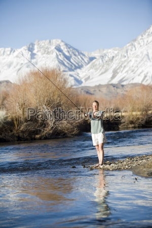 jovem mulher pesca com mosca com