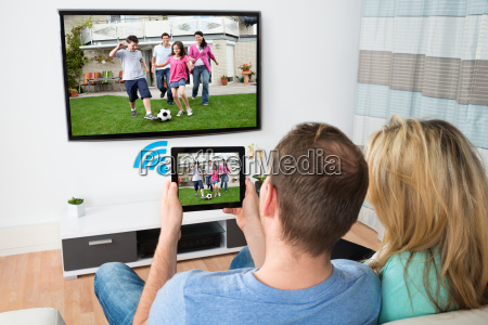 couple connecting television and digital table