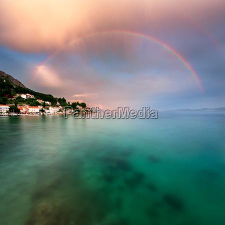 arco iris sobre a praia rochosa