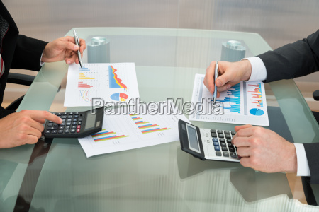 businessmen analyzing the graph on office