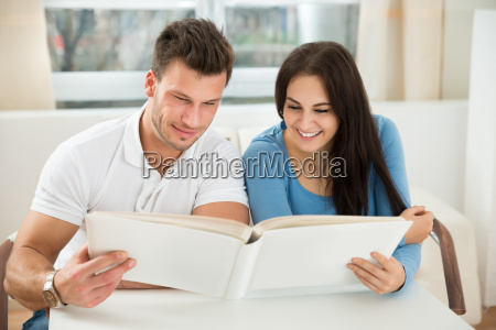 young couple holding green house model
