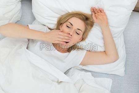 mulher de bocejo no quarto