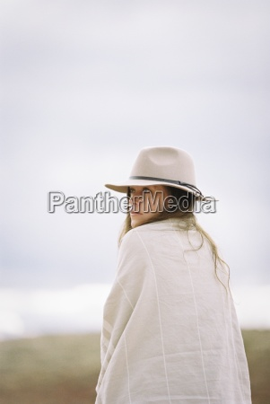 woman wearing a hat and wrap