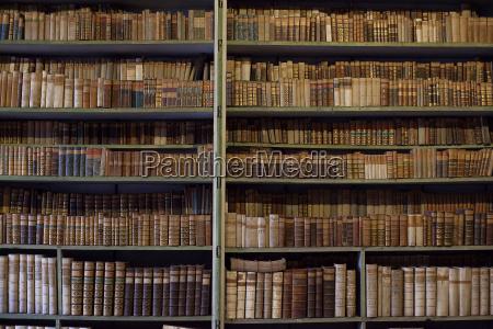 velhos livros historicos em biblioteca estante