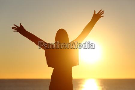 mulher livre que levanta o sol