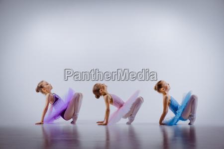 tres ballet meninas sentadas em tutus