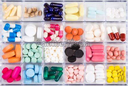 varios comprimidos e capsulas no recipiente