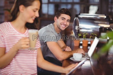 smiling young man sitting at bar