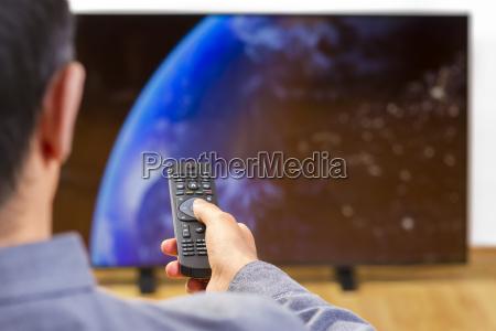 homem com controle remoto assistindo tv