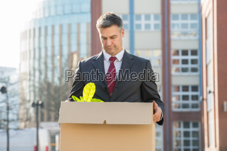 businessman standing with cardboard box outside
