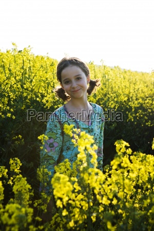girl standing in field of canola
