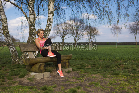 blond female jogger sit outside on