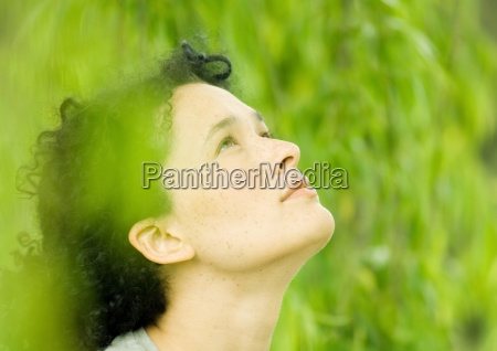 young woman looking up green in