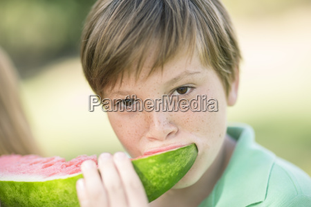 portrait of boy eating slice of