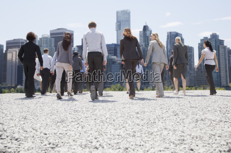 business people walking toward city