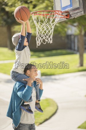 father and son playing basketball in