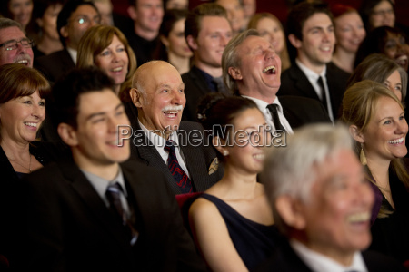 people smiling and laughing in theater